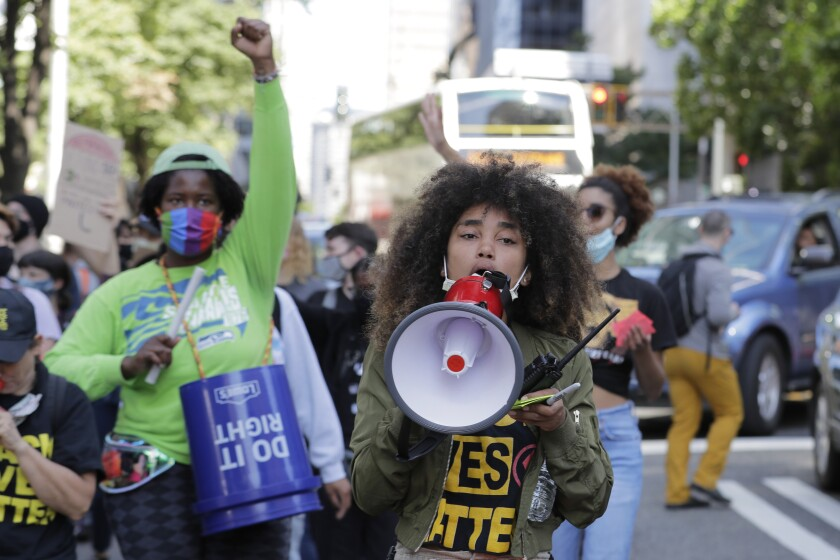 Protesters chant as they march near City Hall, Monday, July 13, 2020, following a news conference held by Seattle Mayor Jenny Durkan, Police Chief Carmen Best, and Fire Chief Harold Scoggins. Durkan and Best were critical of a plan backed by several city council members that seeks to cut the police department's budget by 50 percent. (AP Photo/Ted S. Warren)