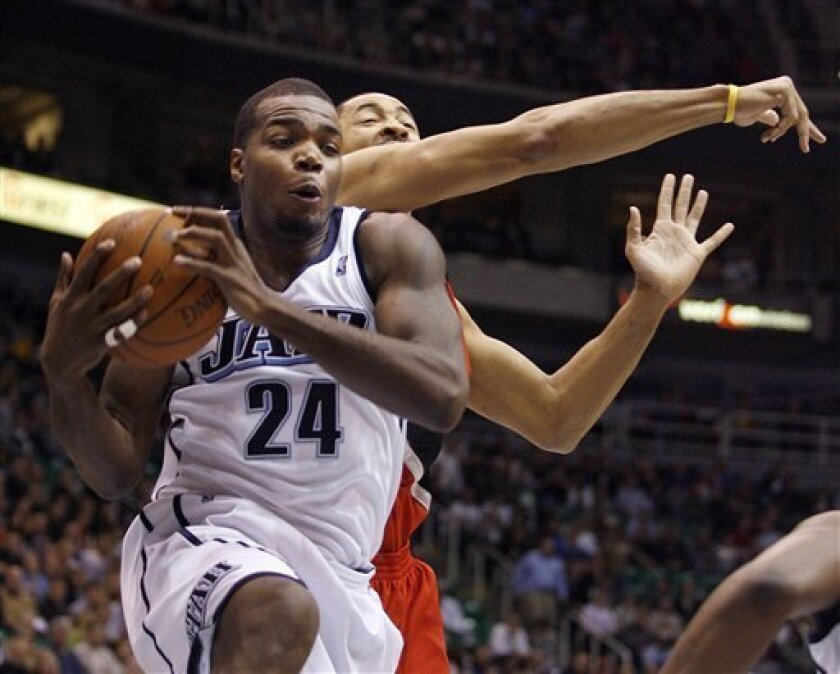 Utah Jazz forward Paul Millsap (24) comes away with a rebound against Portland Trail Blazers center Juwan Howard, right, during the first half of an NBA basketball game Wednesday, Feb. 3, 2010, in Salt Lake City. (AP Photo/Steve C. Wilson)