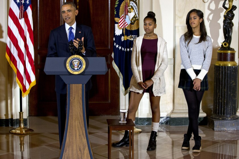 President Barack Obama, joined by his miniskirt-clad daughters Malia, right, and Sasha, center, speaks during the presidential turkey pardoning ceremony, an annual Thanksgiving tradition.
