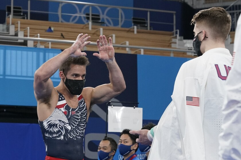 Samuel Mikulak, of United States, greets a team member after his routine on the parallel bars during the artistic men's team final at the 2020 Summer Olympics, Monday, July 26, 2021, in Tokyo. (AP Photo/Gregory Bull)