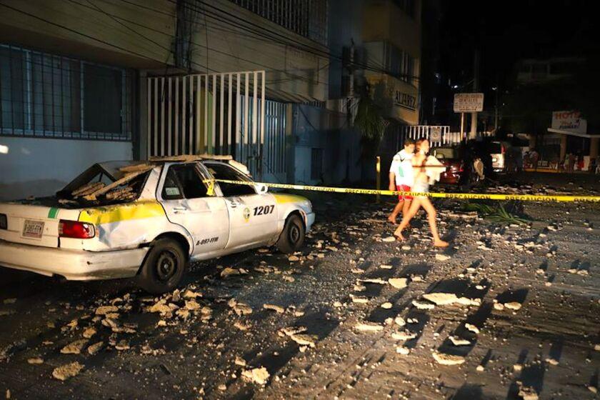 Una pareja pasa junto a un taxi que resultó dañado por la caída de escombros