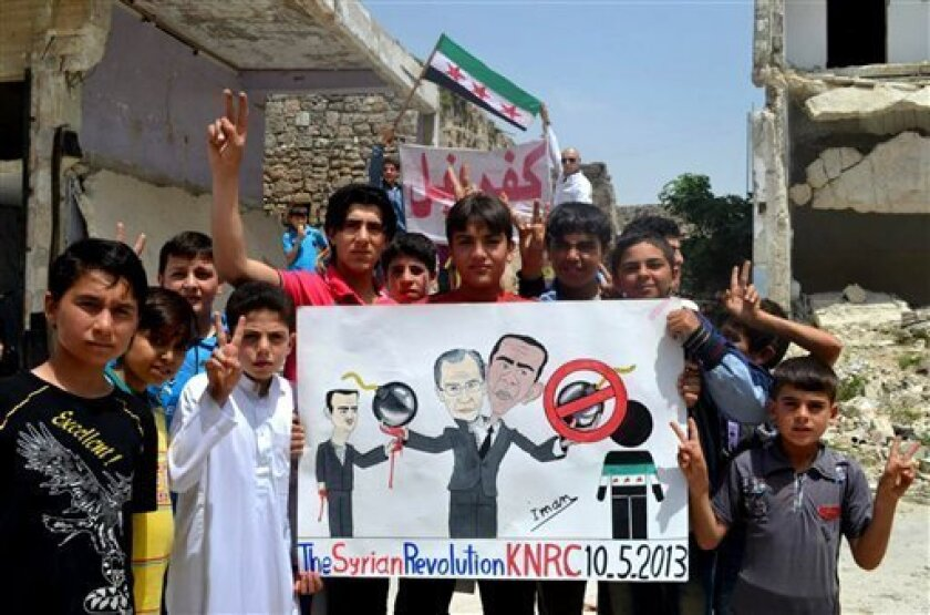 """In this citizen journalism image provided by Edlib News Network, ENN, which has been authenticated based on its contents and other AP reporting, anti-Syrian regime protesters hold a poster depcting Syrian President Bashar Assad, left, Russian Foreign Minister Sergei Lavrov, center, and U.S. President Barack Obama, right during a demonstration, at Kafr Nabil town, in Idlib province, northern Syria, Friday May 10, 2013. Arabic on the banner background reads, """"Kafr Nabil."""" (AP Photo/Edlib News Netw"""