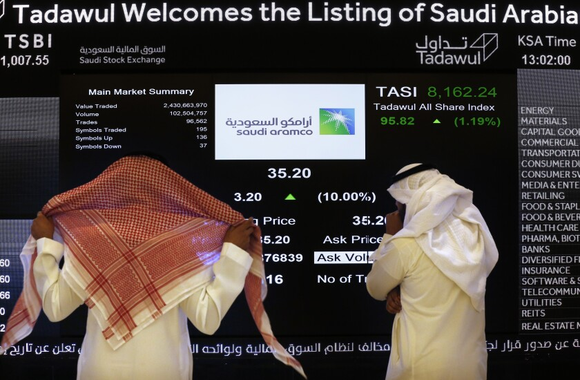 "FILE- In this Dec. 11, 2019, file photo, the Saudi stock market officials watch the stock market screen displaying Saudi Arabia's state-owned oil company Aramco after the debut of Aramco's initial public offering (IPO) on the Riyadh's stock market in Riyadh, Saudi Arabia. Saudi Arabian oil company Aramco's initial public offering raised $29.4 billion, more than previously announced after the company said Sunday it used a so-called ""greenshoe option"" to sell an additional 450 million shares to satiate investor demand. (AP Photo/Amr Nabil)"