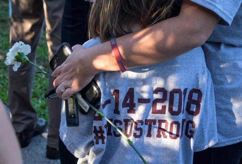 Una madre abraza a su hija mientras padres y estudiantes llegan a la escuela Marjory Stoneman Douglas en Parkland, Florida.