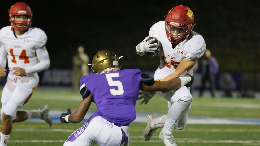 Cathedral Catholic running back Shawn Poma gets past St. Augustine's Isaac Taylor-Stuart during Friday night's Holy Bowl showdown.