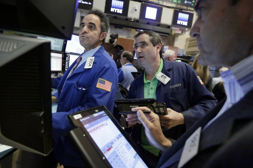 Specialist Jorge Fernandez. left, works with traders Daniel Trimble, center, and Mark Muller on the floor of the New York Stock Exchange, Friday, June 3, 2016. Stocks are broadly lower in early trading and bond prices are higher after the government reported a sharp slowdown in hiring last month. (