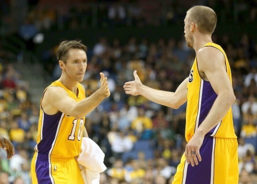 Lakers point guard Steve Nash high-fives teammate Steve Blake as he enters a preseason game against the Trail Blazers.
