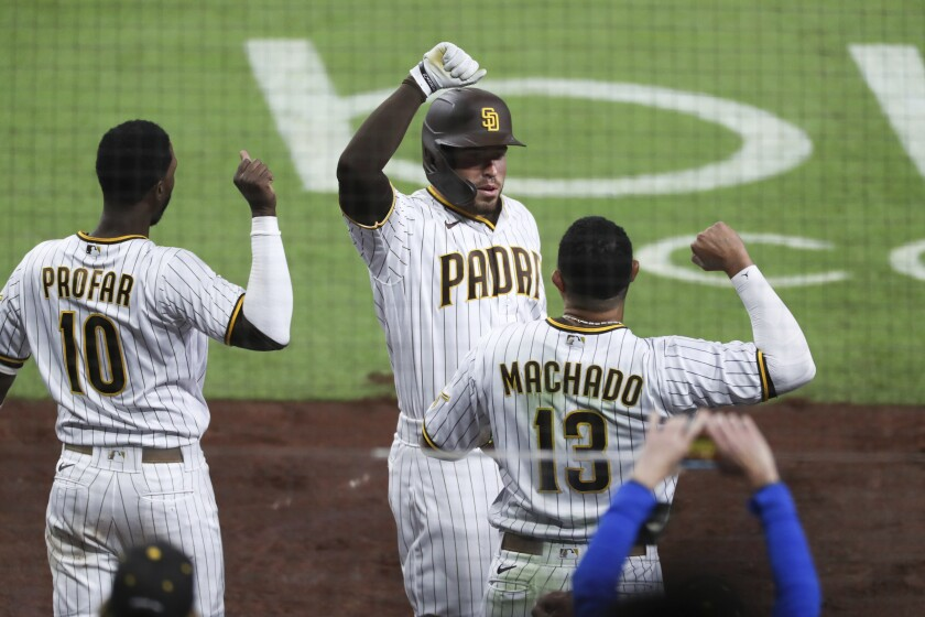 San Diego Padres' Victor Caratini, center, is congratulated by Manny Machado, right, after hitting a two-run home run against the San Francisco Giants during the seventh inning of a baseball game Tuesday, April 6, 2021, in San Diego. (AP Photo/Derrick Tuskan)