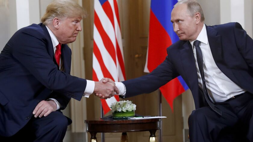 U.S. President Donald Trump, left, and Russian President Vladimir Putin shake hands at the beginning of a meeting at the Presidential Palace in Helsinki, Finland, on July 16.