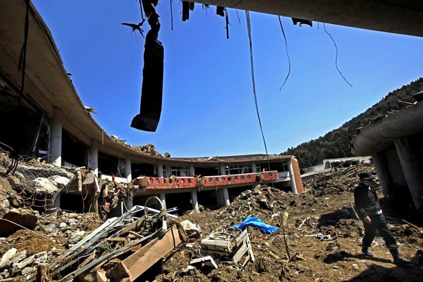 A man walks through the debris at Okawa Elementary School, devastated by an earthquake and tsunami