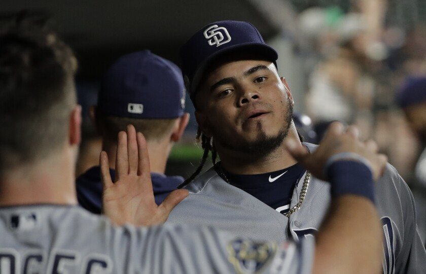Padres starting pitcher Dinelson Lamet, right, is greeted in the dugout during a baseball game against the Seattle Mariners, Tuesday, Aug. 6, 2019, in Seattle. (AP Photo/Ted S. Warren)