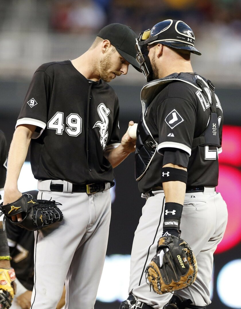 Chicago White Sox catcher Tyler Flowers, right, talks with pitcher Chris Sale in the third inning of a baseball game against the Minnesota Twins, Thursday, April 30, 2015, in Minneapolis. The Twins scored seven runs in the inning. (AP Photo/Jim Mone)