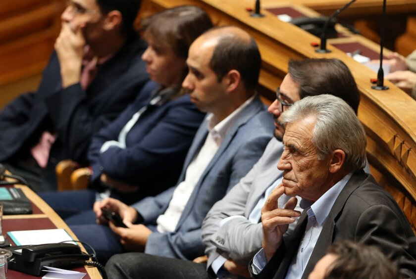 In this Oct. 23 2015 photo, Jeronimo de Sousa, right, leader of the Portuguese Communist Party, attends the first session of the post-election Parliament, in Lisbon. Die-hard communists are poised to walk the corridors of power in Portugal, and a new generation of leftist radicals is right beside t