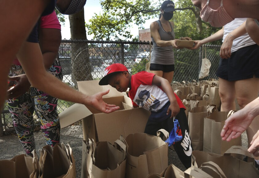 Hunter Stewart, 5, helps pack and deliver food