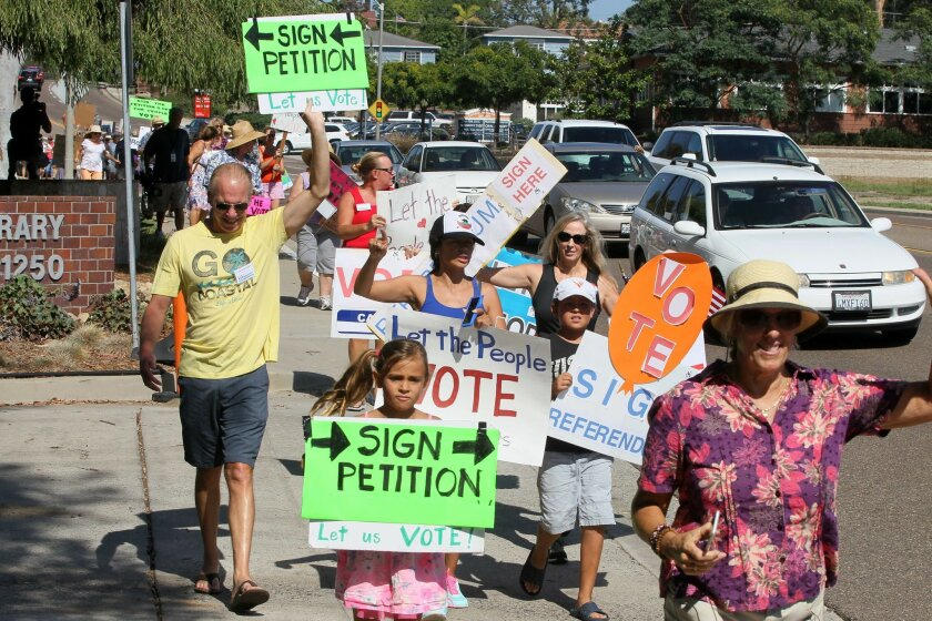 Anti-Caruso project volunteers march down Carlsbad Village Drive in September to City Hall to deliver boxes of referendum petitions.