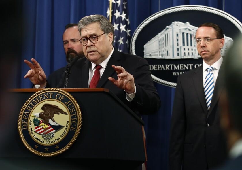 Attorney General William Barr speaks alongside Deputy Attorney General Rod Rosenstein, right, and acting Principal Associate Deputy Attorney General Edward O'Callaghan, left, about the release of a redacted version of special counsel Robert Mueller's report during a news conference Thursday at the Department of Justice in Washington. (AP Photo/Patrick Semansky)