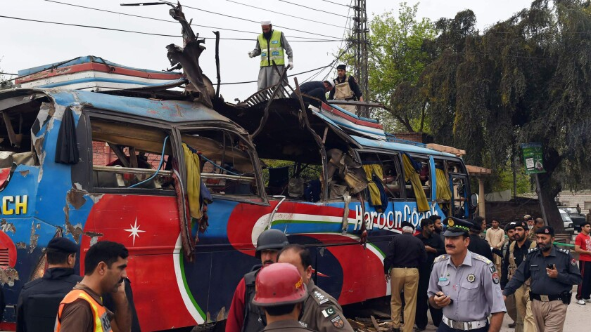 Pakistani volunteers and security forces inspect a destroyed bus after a bomb blast in Peshawar on March 16, 2016.