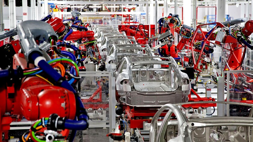 Robots perform vehicle assembly at the Tesla production facility in Fremont, Calif.