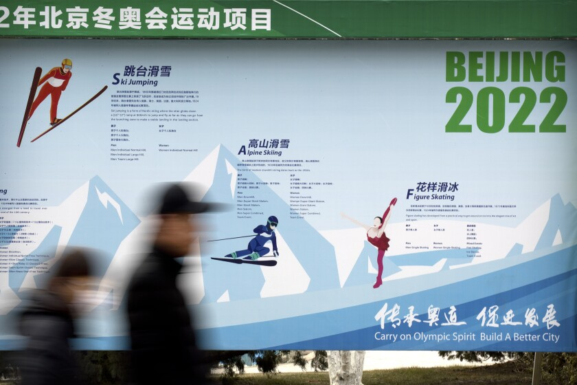 FILE - In this Feb. 6, 2019, file photo, people walk past a display introducing winter sporting events for the upcoming Beijing 2022 Winter Olympics at a temple fair at Longtan Park in Beijing. Organizers of the 2022 Beijing Winter Olympic Games say they are on track to complete all competition venues by year-end and have teams in place for test events, despite the devastating impact of the novel coronavirus outbreak that originated in the country late last year. (AP Photo/Mark Schiefelbein, File)