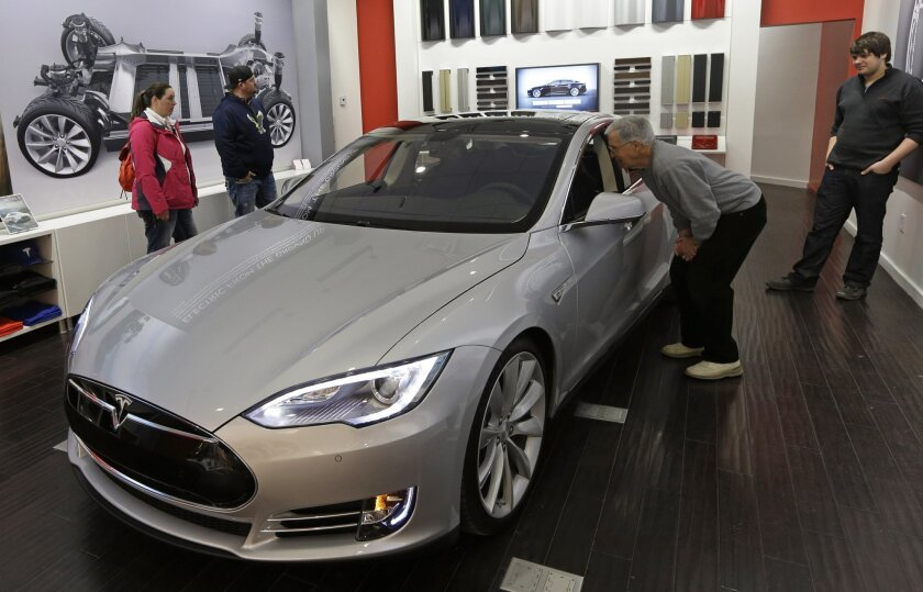 FILE - In this March 17, 2014 file photo, Tesla representative John Van Cleave, right, shows customers Sarah and Robert Reynolds, left, and Vince Giardina, a new Tesla all electric car at a Tesla showroom inside the Kenwood Towne Centre in Cincinnati. Tesla reports quarterly financial results on Tu