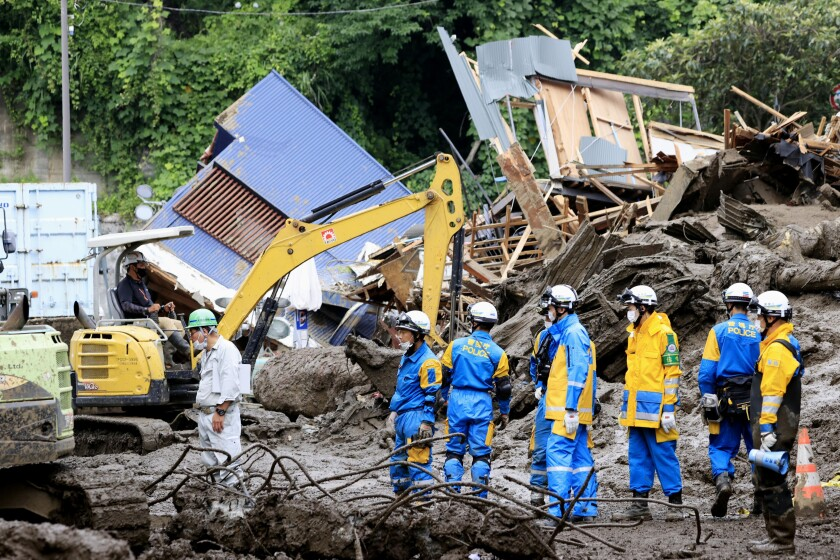 Police officers continue a search operation for missing people at the site of a mudslide in Atami, southwest of Tokyo Tuesday, July 6, 2021. Rescue workers struggled with sticky mud and risks of more mudslides Tuesday as they searched for people may have been trapped after a torrent of mud that ripped through a seaside hot springs resort. (Kyodo News via AP)