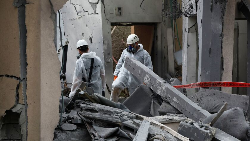 In Mishmeret, north of Tel Aviv, Israeli police examine a house struck by a missile reportedly fired by militants from the Gaza Strip on March 25, 2019.