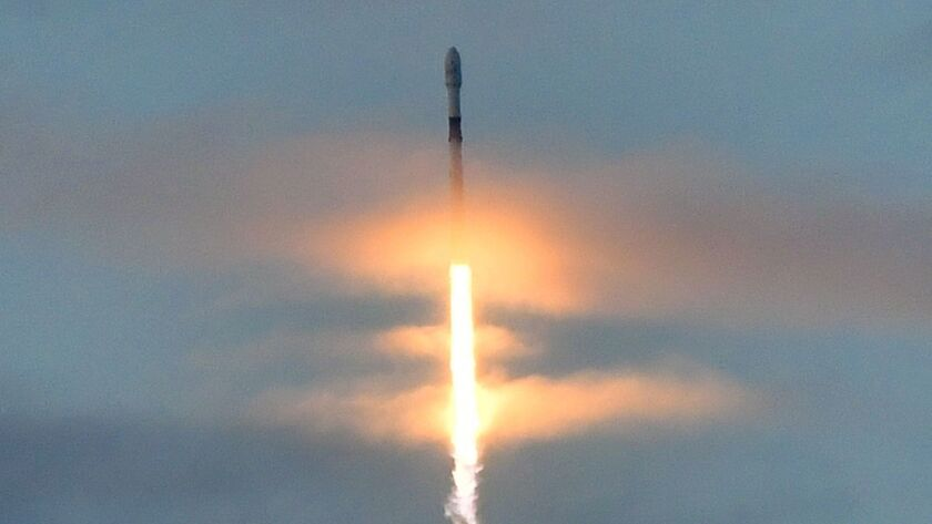 A SpaceX Falcon 9 rocket carrying 10 Iridium Communications satellites blasts off through clouds ove