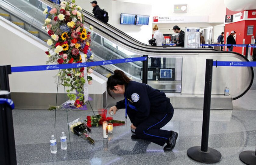 Transportation Security Administration officer Alexa Mendoza lights a candle at a memorial to TSA officers killed and wounded at Terminal 3 at Los Angeles International Airport.