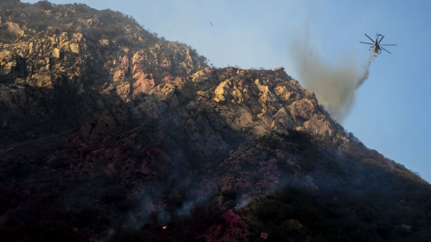 MALIBU, CALIF. -- SUNDAY, NOVEMBER 11, 2018: A helicopter drops water on a hot spot in steep terrain