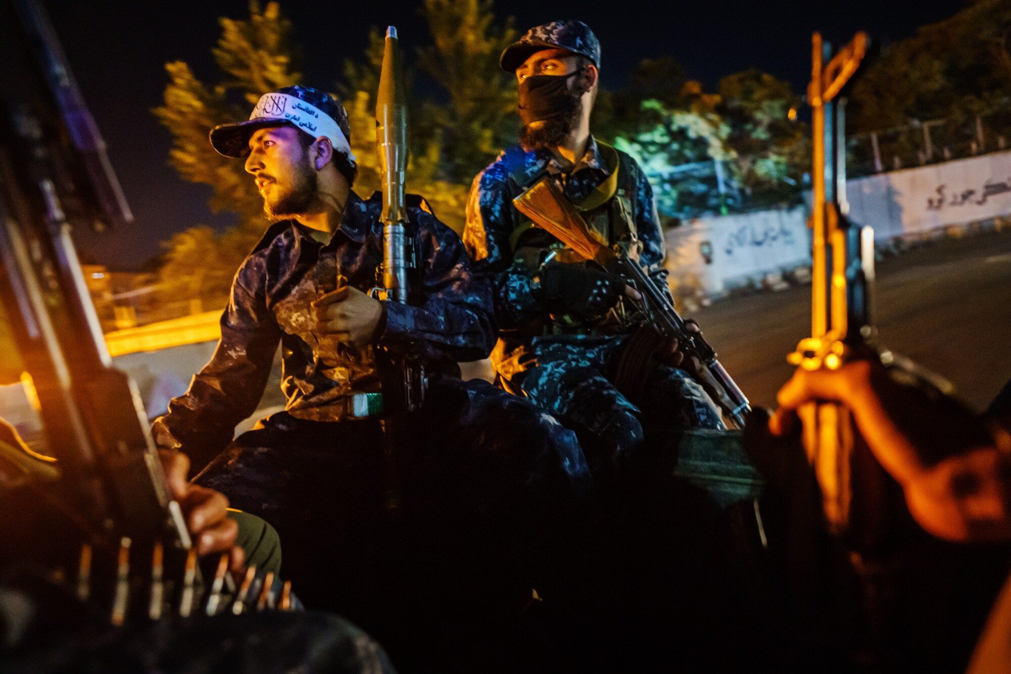 Men with rifles ride in a vehicle at night
