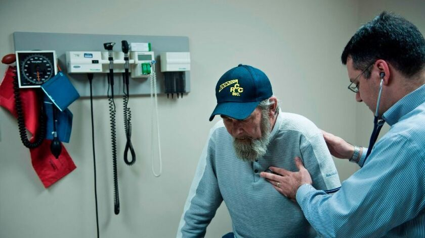 Don Humbertson, a 64-year-old lung cancer survivor, is examined by Dr. Wade Harvey at a community health center in Blacksville, W.Va.