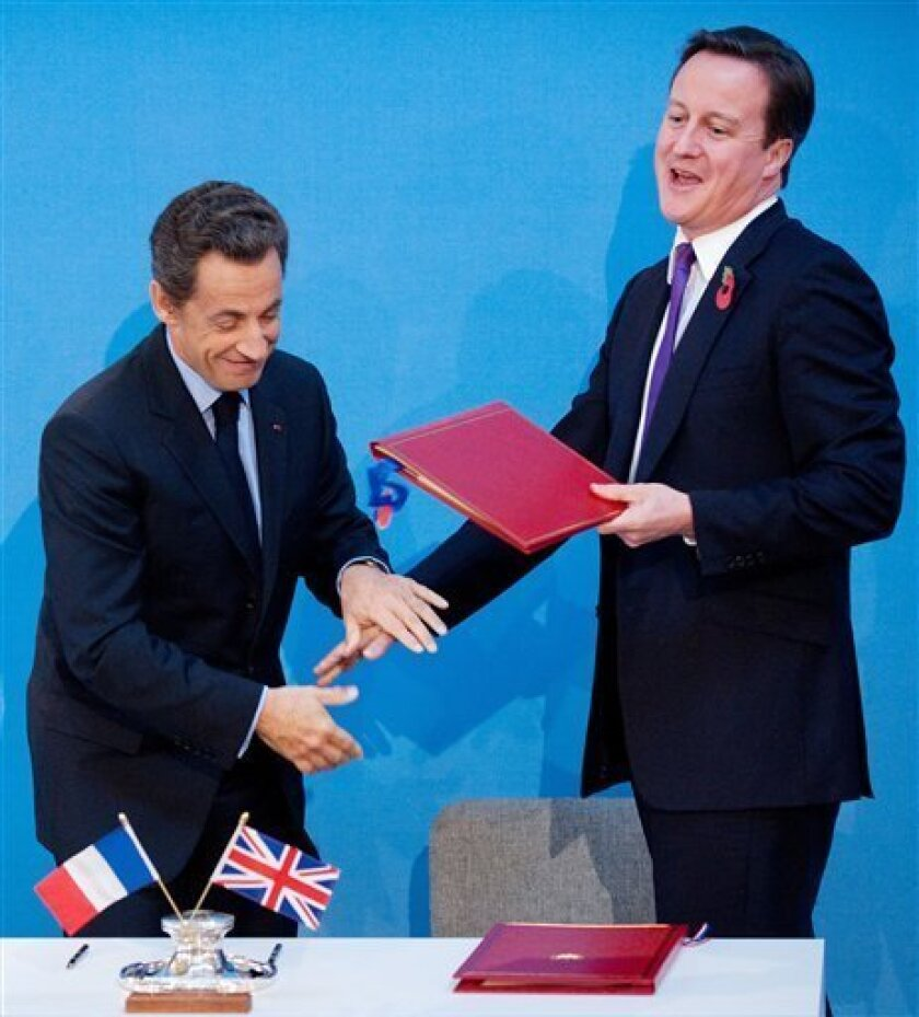 French President Nicolas Sarkozy, left, and Britain's Prime Minister David Cameron joke after signing a treaty at an Anglo-French summit at Lancaster House in London, Tuesday Nov. 2, 2010. Britain and France vowed to work hand-in-glove as their leaders ushered in an unprecedented era of defence cooperation by agreeing to create a joint force and share nuclear test facilities.(AP Photo/Leon Neal, pool)
