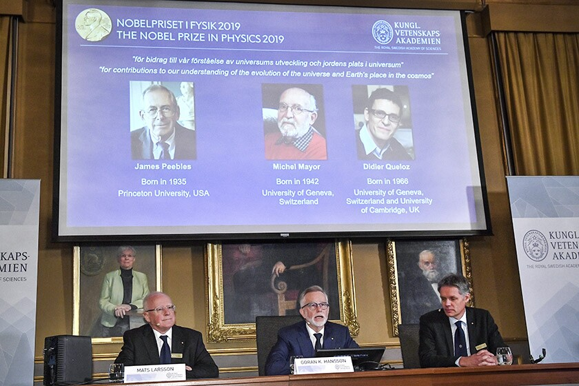 Images of the winners of the Nobel Prize in physics are projected on a screen during a news conference in Stockholm: from left, James Peebles, Michel Mayor and Didier Queloz.