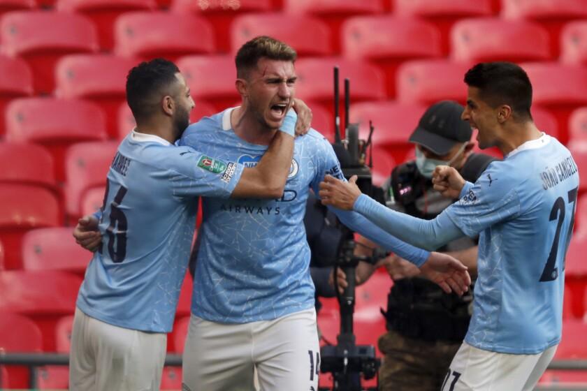 Aymeric Laporte, centro, del Manchester City, es felicitado por Riyad Mahrez, izquierda, y Joao Cancelo tras anotar el primer gol de la final de la Copa de la Liga inglesa ante el Tottenham, en el estadio Wembley de Londres, el domingo 25 de abril de 2021. (AP Foto/Alastair Grant)