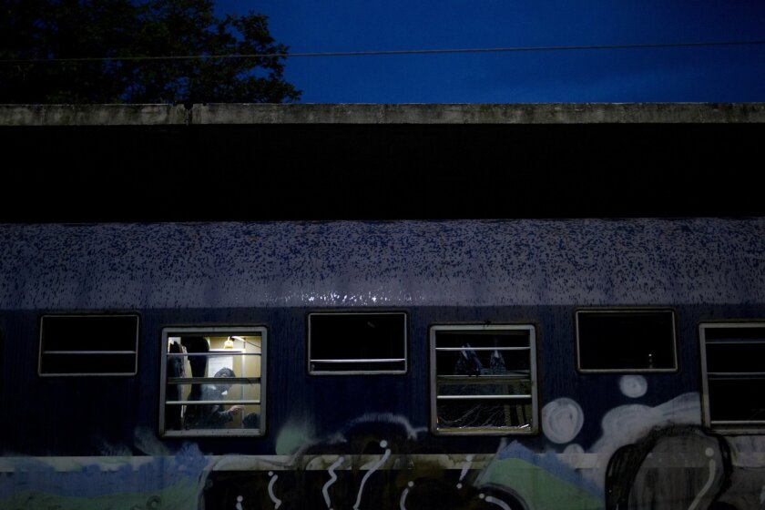 In this Tuesday, May 10, 2016 photo, drops of rain cover a train as a man is seen inside  train sleeper carriages that he lives in the sprawling refugee and migrant tent city of Idomeni, on Greece's northern border with Macedonia. (AP Photo/Petros Giannakouris)