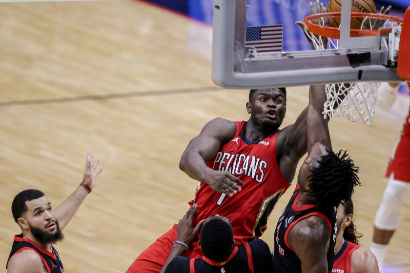 New Orleans Pelicans forward Zion Williamson (1) shoots over Toronto Raptors forward Chris Boucher (25) and forward OG Anunoby (3) during the second half of an NBA basketball game on Saturday, Jan. 2, 2021, in New Orleans. (AP Photo/Butch Dill)