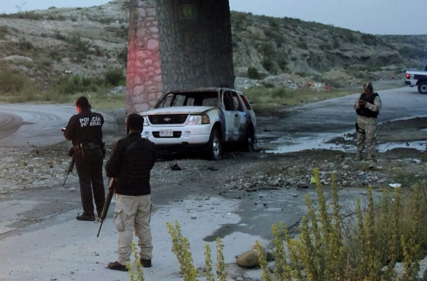 Mexican policemen inspect the site where they reported finding the bodies of five charred people on July 18. The state of Coahuila, where this incident took place, has had 18 people slain in recent days.