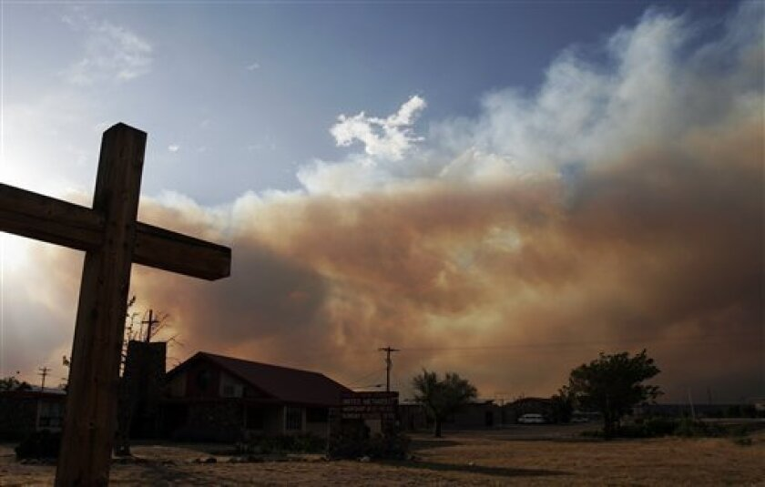 Smoke rolls up behind the United Methodist Church on Hwy 30 between Santa Clara Pueblo and Española on Thursday June 30, 2011. A raging blaze that has become one of the largest forest fires in New Mexico history left the leader of one Native American community with a sinking feeling Thursday as it