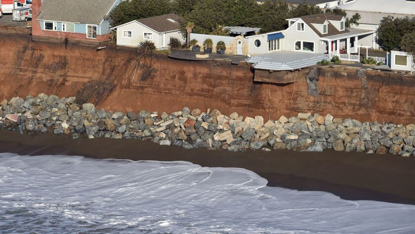 Houses hang on the edge of an eroding cliff in Pacifica, Calif.
