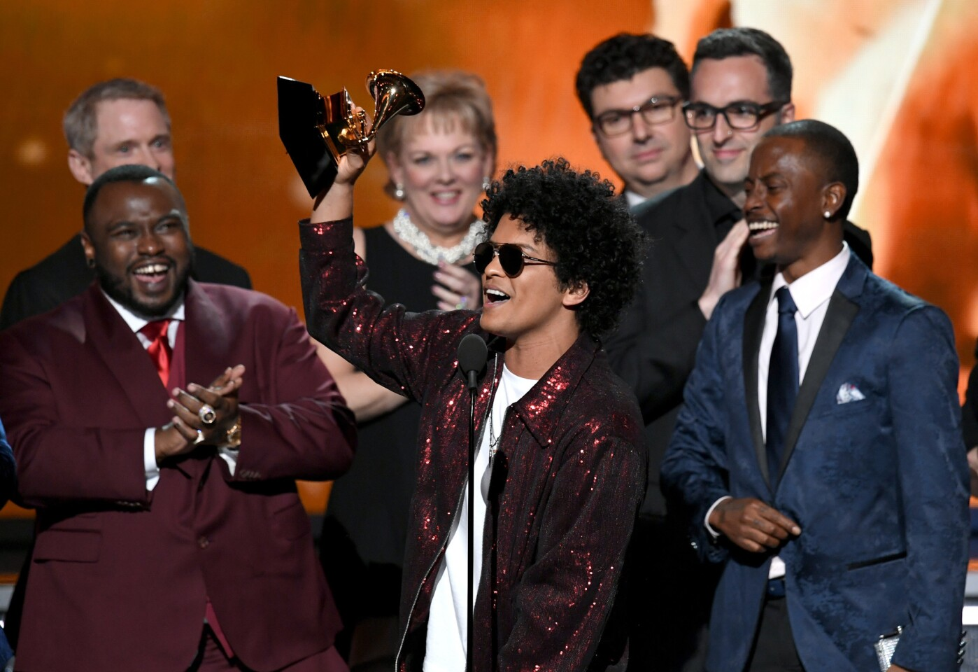 "Bruno Mars, center, accepts album of the year for ""24K Magic"" with his production team onstage."