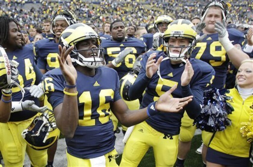 Michigan quarterbacks Denard Robinson (16) and Tate Forcier (5) lead a cheer by the student section after their college football game against Bowling Green in Ann Arbor, Mich., Saturday, Sept. 25, 2010. Michigan defeated Bowling Green 65-21. (AP Photo/Carlos Osorio)
