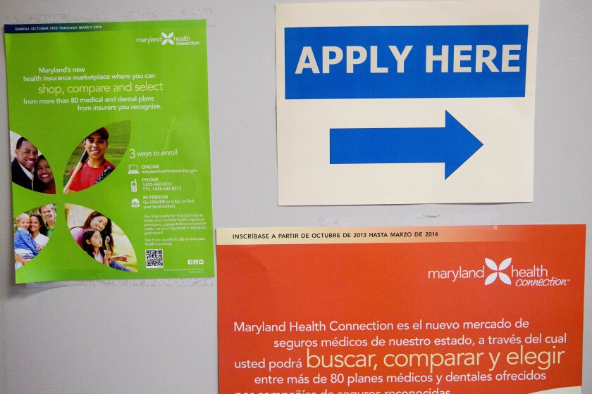 "An ""Apply Here"" sign hangs at a health insurance education and enrollment event in Silver Spring, Md."