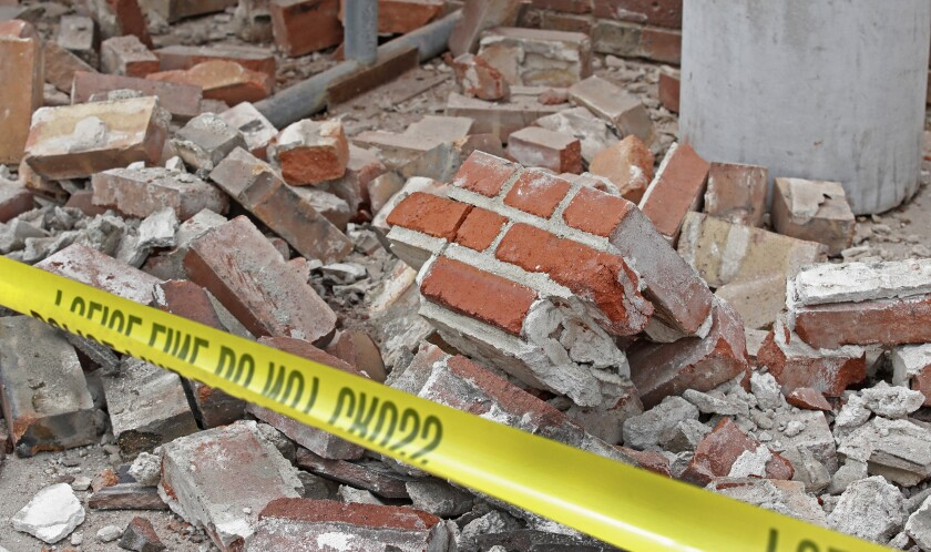 Bricks and debris lay at the base of a building damaged by an earthquake on March 18, 2020 in Magna, Utah.
