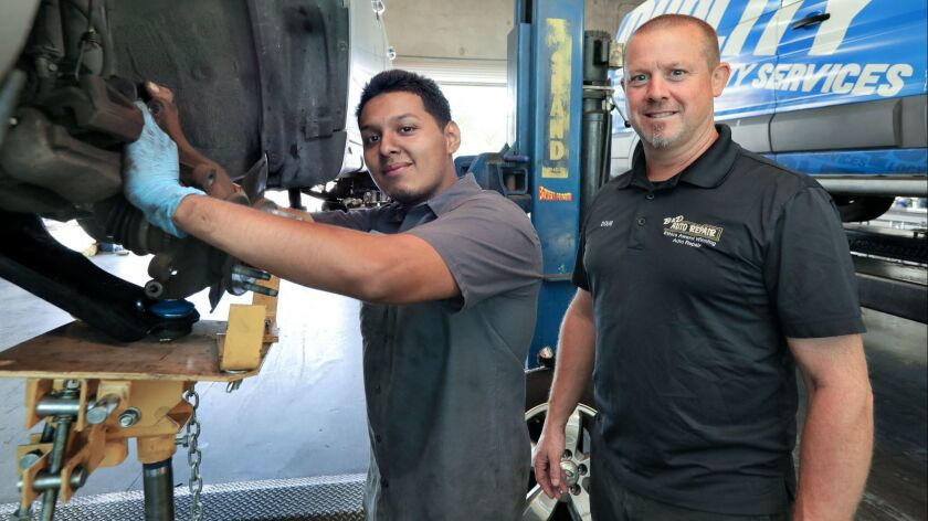 Portrait of Doug Jones, at right, owner of B&D Auto Repair, with Fausto Alvarado, one of the mechanics employed there.