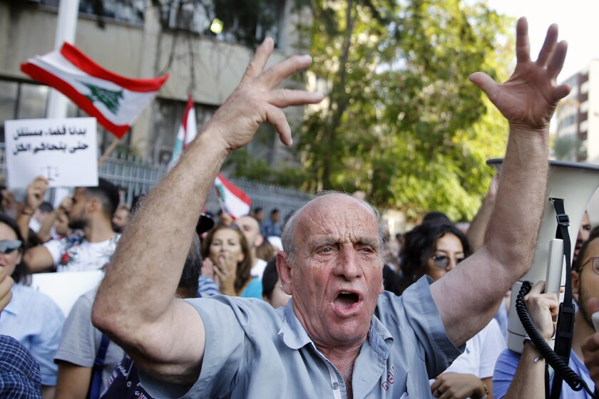 An anti-government protester chants slogans during ongoing protests against the Lebanese government, in front of the Justice Palace in Beirut, Lebanon, Wednesday, Nov. 6, 2019. Protesters are demonstrating outside state institutions in an effort to keep up the pressure on top leaders to form a new government after the current one resigned. (AP Photo/Bilal Hussein)