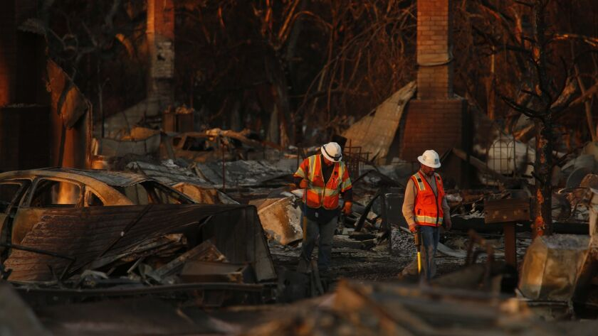 PG&E workers inspect a fire-ravaged neighborhood of Coffey Park in Santa Rosa in October.