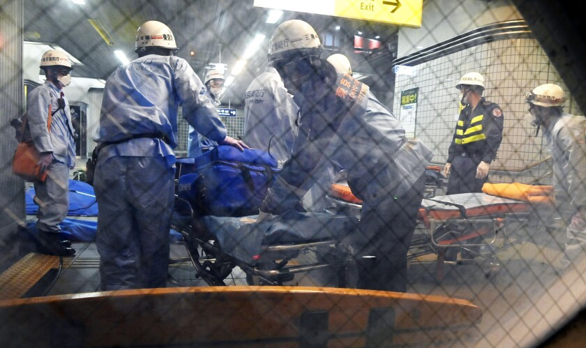 Rescuers prepare stretchers at Tokyo's Soshigaya-Okura Station after a Friday stabbing on a commuter train.