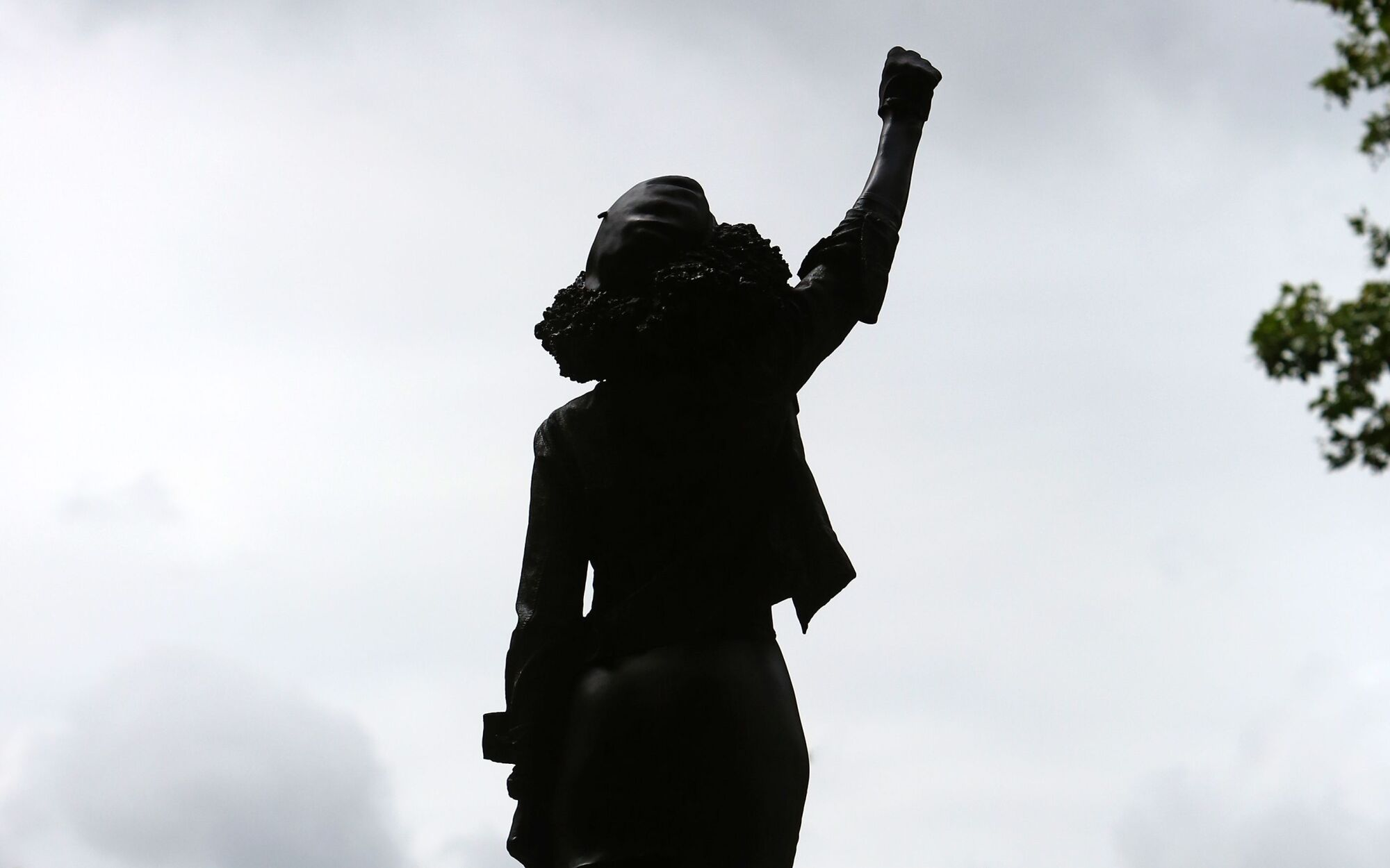 A statue of Jen Reid with an arm raised in a Black Power salute