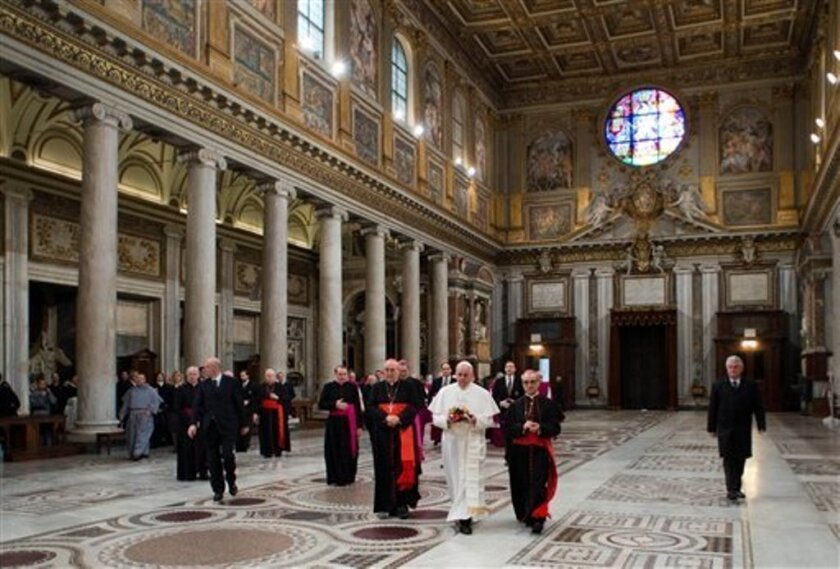 In this photo provided by the Vatican newspaper L'Osservatore Romano, Pope Francis,center, flanked at left by Cardinal Agostino Vallino, and at right by Cardinal Santos Abril y Castello, walks inside St. Mary Major Basilica, in Rome, Thursday, March 14, 2013.