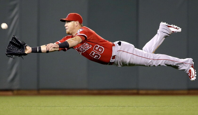 Angels right fielder Kole Calhoun makes a diving catch on a shallow fly ball hit by San Francisco's Andrew Susac during a 2-1 loss to the Giants on May 1. Calhoun will get offense help with baseman/outfielder Marc Krauss from triple-A Salt Lake, inserted into the ninth spot in the lineup against the Rockies on Tuesday.